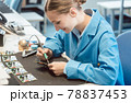 Worker in electronics manufacturing soldering a component 78837453