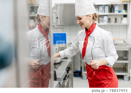 Cook in large commercial kitchen stirring sauce 78837455