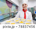 Cook in commercial kitchen showing tray with dessert 78837456
