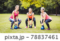 Women doing exercise with kettle bell in park 78837461