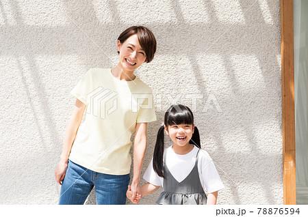 日向ぼっこしながら手をつなぐ女の子と母親 78876594