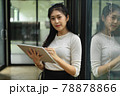 Female teenager looking into camera while standing and using digital tablet 78878866