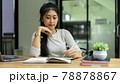 Portrait of female student reading book to prepare for upcoming exam at home 78878867