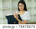 Portrait of female teenager with eyeglasses reading book in library 78878878