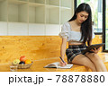 Young female teenager studying with digital tablet and stationery in relax corner 78878880