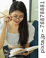 Cropped shot of female teenager with eyeglasses reading book in reading corner 78878881