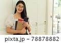 Portrait of female teenager with eyeglasses holding books 78878882