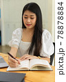 Cropped shot of female college student reading book to prepare for exam 78878884