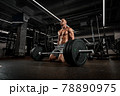 A bodybuilder is going to lift a barbell, work in a gym with large weights, training with a sports equipment, a heavy barbell. 78890975
