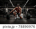 Handsome athlete in good shape preparing the barbell for training, achieving success through stubborn and hard training 78890976
