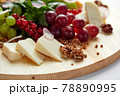 Assortment of cheeses and grapes on a wooden background, close-up, light background, mix of Italian cheeses in backlight. 78890995