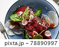 Cold smoked beef jerky close-up, brisaola with lettuce in a blue plate close-up, advertising shot 78890997
