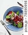 Bresaola with Korean salad, beef jerky close-up with lettuce in a blue plate, top view. 78890998