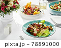 Baked eggplants with cheese, on the table surrounded by other Italian dishes, banquet table, light tablecloths 78891000