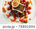 Black cod with vegetables on a light dish, baked black cod shot from above, close-up, copy space 78891004