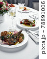 Festive table with fish dishes and glasses of wine, grilled flounder sea bass on a light table with white wine, wedding table concept 78891006