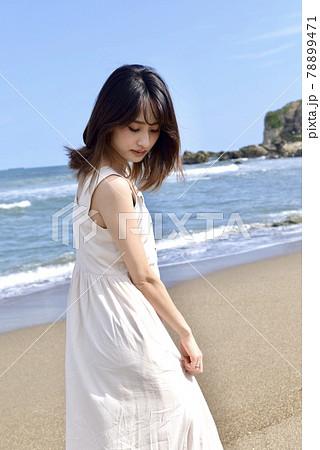 晴れた日の海岸でポーズをとるワンピース姿の若い女性 78899471