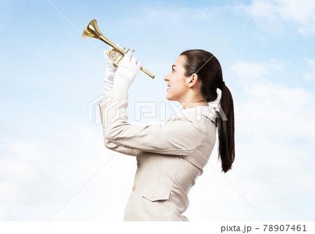 Woman playing trumpet brass instrument 78907461