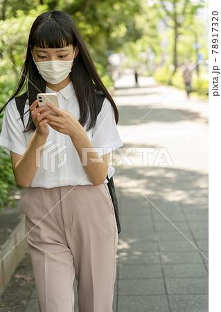 マスクをして歩きスマホをする10代女性 78917320