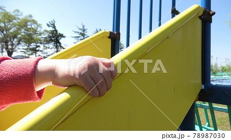 滑り台を逆から登る小さな男の子の手 78987030