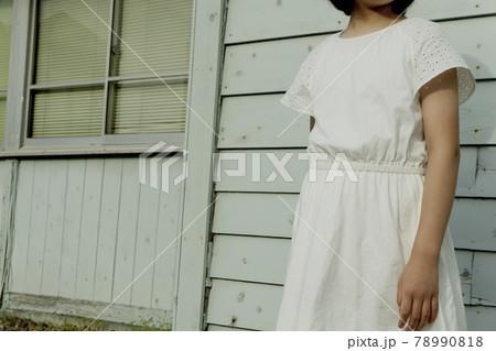 レトロな水色の壁の前に立つ女の子 78990818