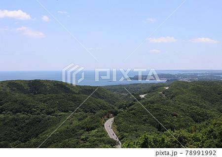高台から見たバイクの行く道路と緑深き山と海と町の見える風景 78991992