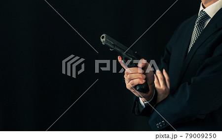 拳銃を構えるスーツの人物 79009250