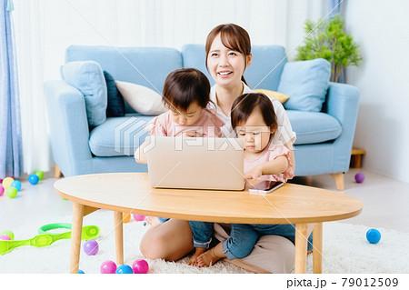リビングで双子の姉妹とノートパソコンを使うママ 79012509