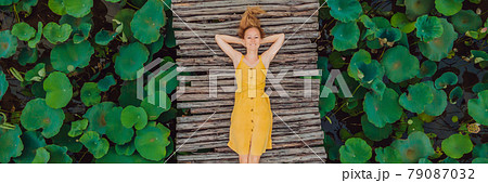 BANNER, LONG FORMAT Young woman in a yellow dress on the path among the lotus lake. Mua Cave, Ninh Binh, Vietnam. Vietnam reopens after quarantine Coronovirus COVID 19 concept 79087032