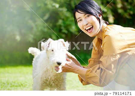 庭で愛犬と戯れるミドル女性 79114171