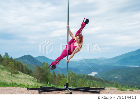 Beautiful red-haired woman dancing on a portable platform on a background of mountains. The girl moves sexually next to the pole. Jumpsuit for classes. high heels. Altai. Awesome flexibility. 79114411