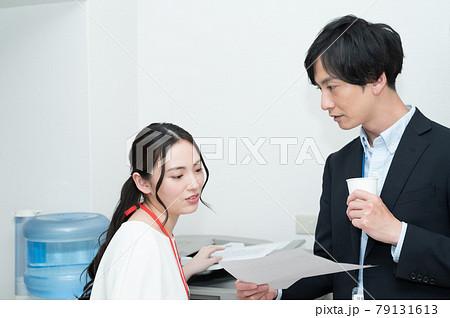 コピー機の前で書類について話し合う上司と部下 79131613