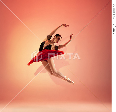 Young and incredibly beautiful ballerina is posing and dancing at red studio full of light. 79146672