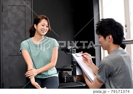 会話をするジムのインストラクター(トレーナー)の男性と会員の女性 79171374