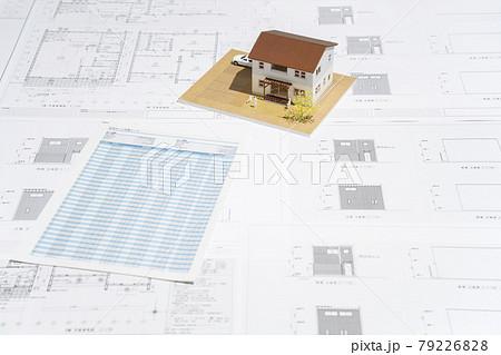 テーブルの上に建築図面の資料と住宅模型がある風景 79226828