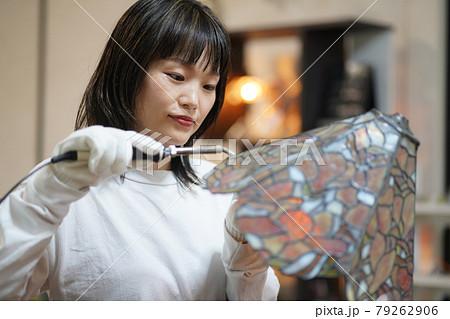 ステンドグラスのランプを作る女性 79262906