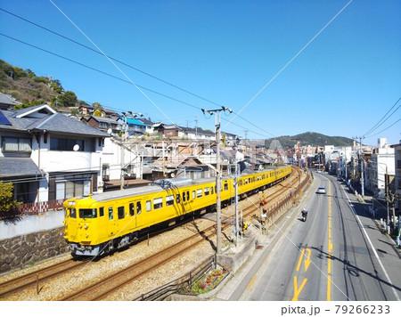 尾道の古い街並みを走り抜ける列車 79266233