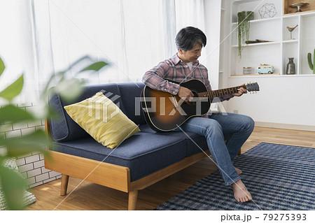 リビングでアコースティックギターを弾く中高年の男性 79275393