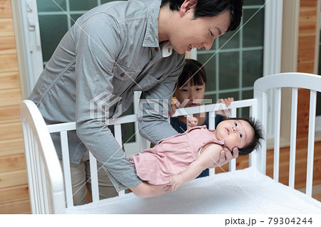 新生児を抱っこしてベッドに寝かしつけをするパパ 79304244