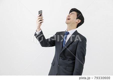 Asian man businessman laughing at smartphone 79330600