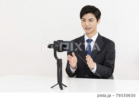Asian young man in suit preparing untact online interview using smartphone 79330630