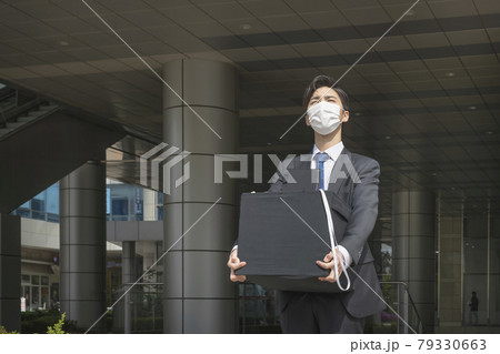 Asian man employee with mask leaving office with box due to lay off, covid 19 effects in business 79330663