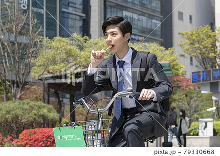 lively, cheerful Asian handsome man going to work with bicycle 79330668