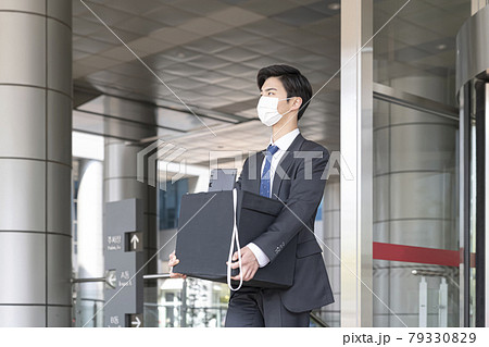 Asian man employee with mask leaving office with box due to lay off, covid 19 effects in business 79330829