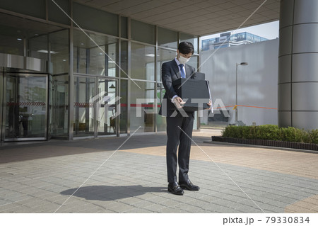 Asian man employee with mask leaving office with box due to lay off, covid 19 effects in business 79330834