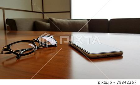 木製テーブルに置かれたスマホと眼鏡 モダンなインテリア 79342267