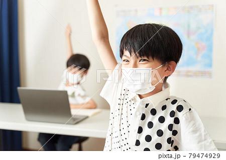教室で手を挙げるマスク着用の小学生 79474929