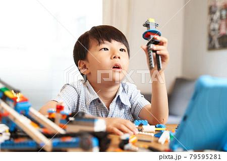 プログラミング教材を組み立てる男の子 79595281