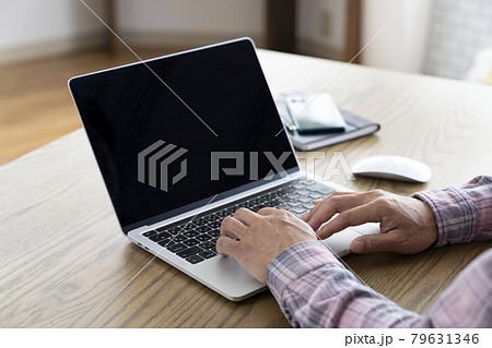 ノートパソコンを操作する50代男性の手元 79631346