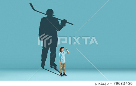 Childhood and dream about big and famous future. Conceptual image with boy and shadow of fit male hockey player on blue background 79633456